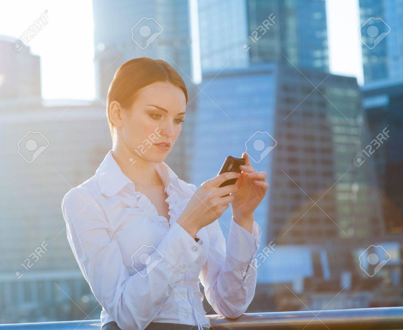 Business woman using smartphone. Sun beams, lens flare - 19203115