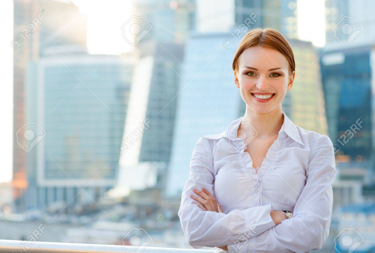 Smiling young business woman on the modern city downtown background - 19203112