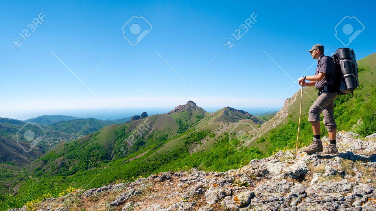 Hiker standing on a stone ridge and enjoys landscape - 19980112