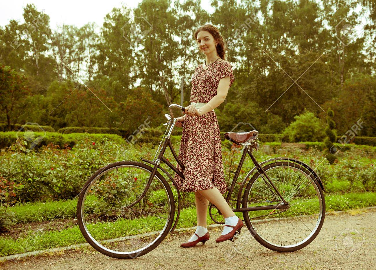 Young woman in dress posing with retro bicycle in the park  Vintage