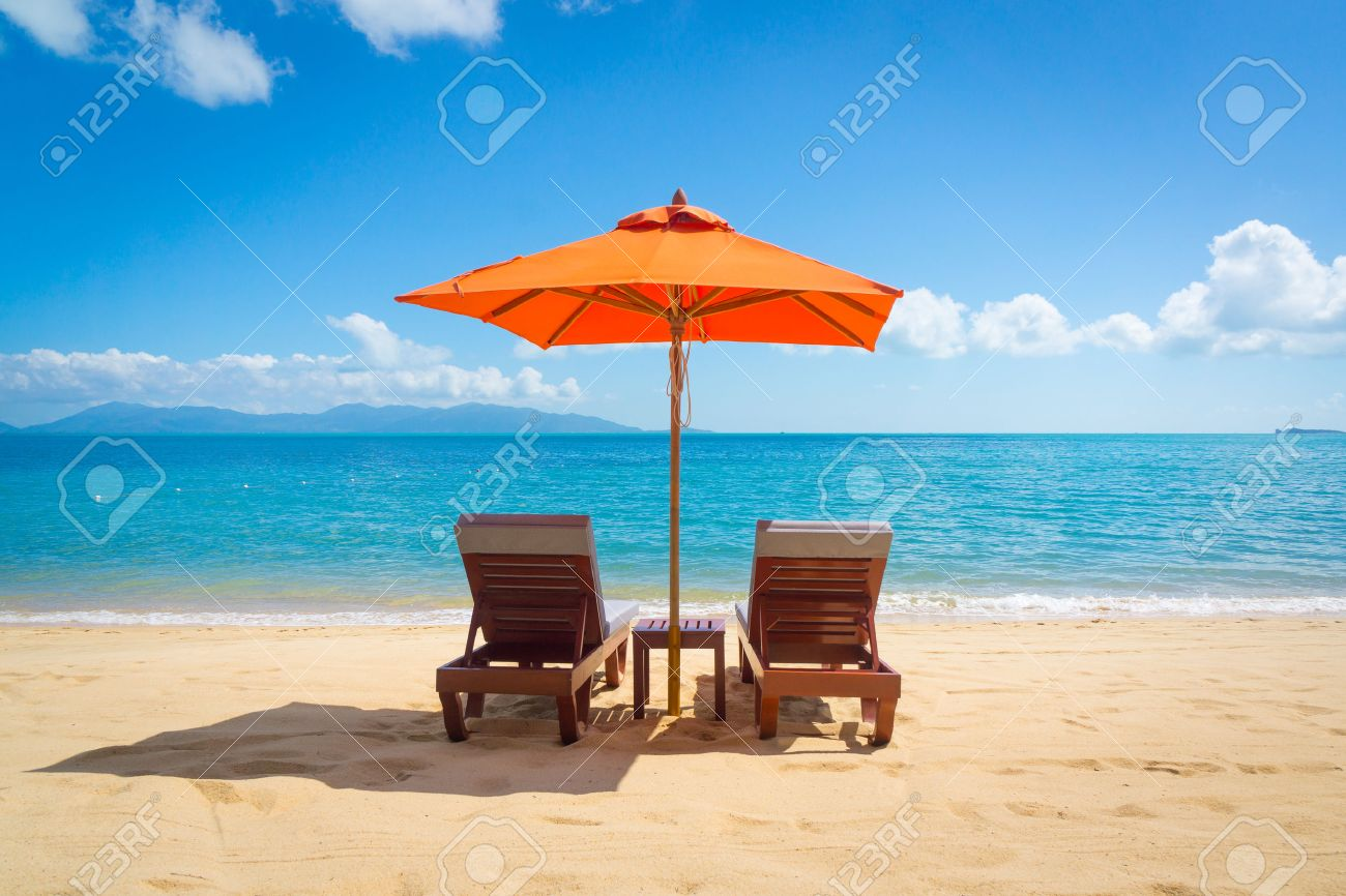Two lounge chairs with sun umbrella on a beach - 28350692
