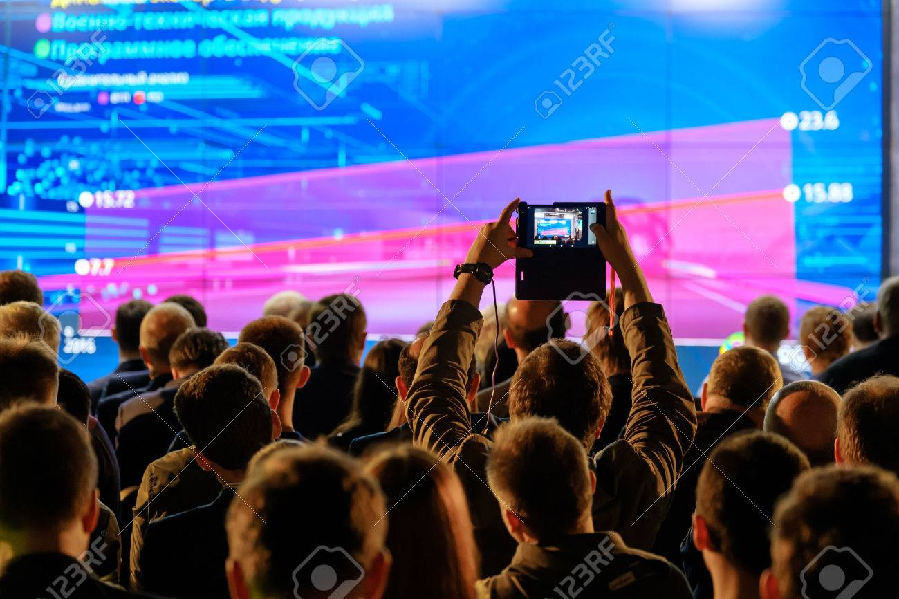 Man takes a picture of the presentation at the conference hall using smartphone - 78534199