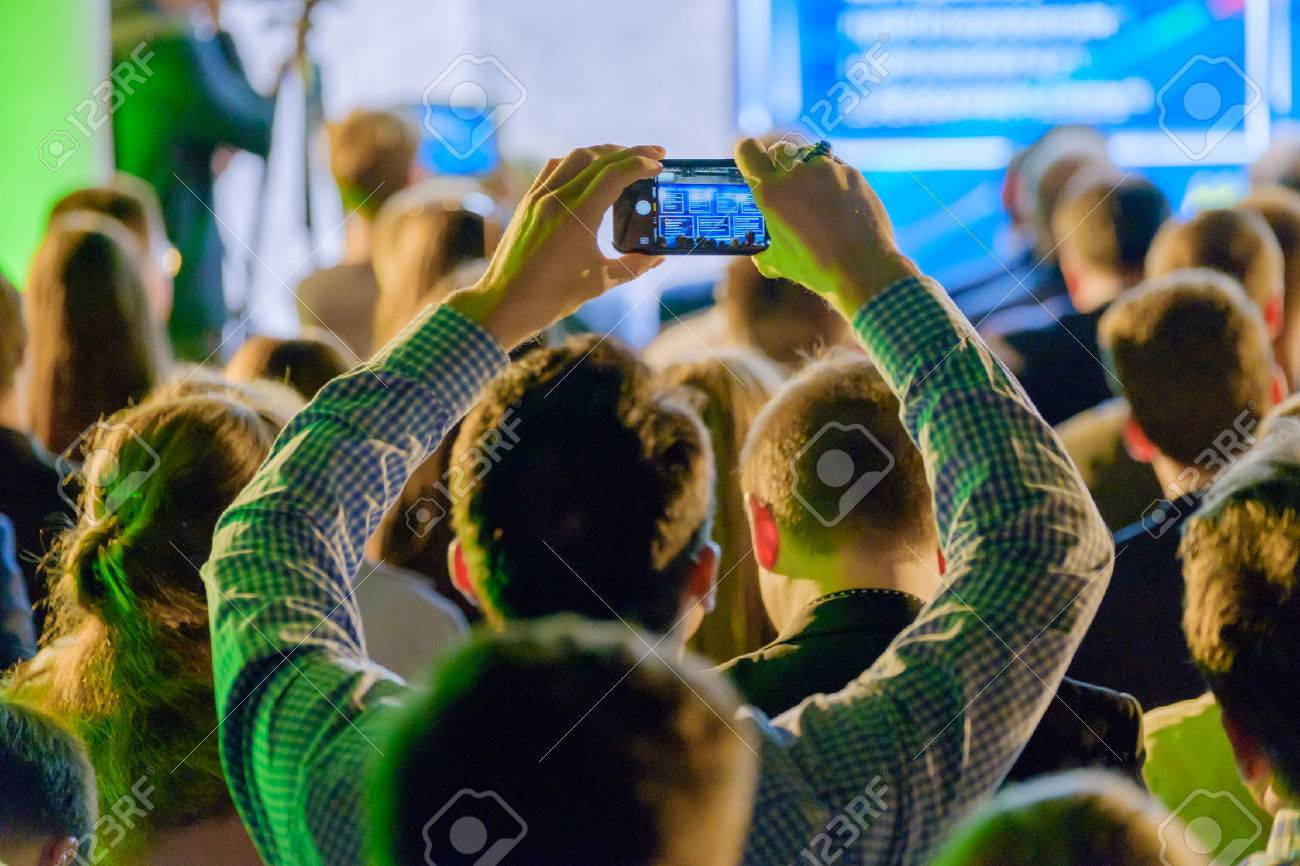 Man takes a picture of the presentation at the conference hall using smartphone - 84946539