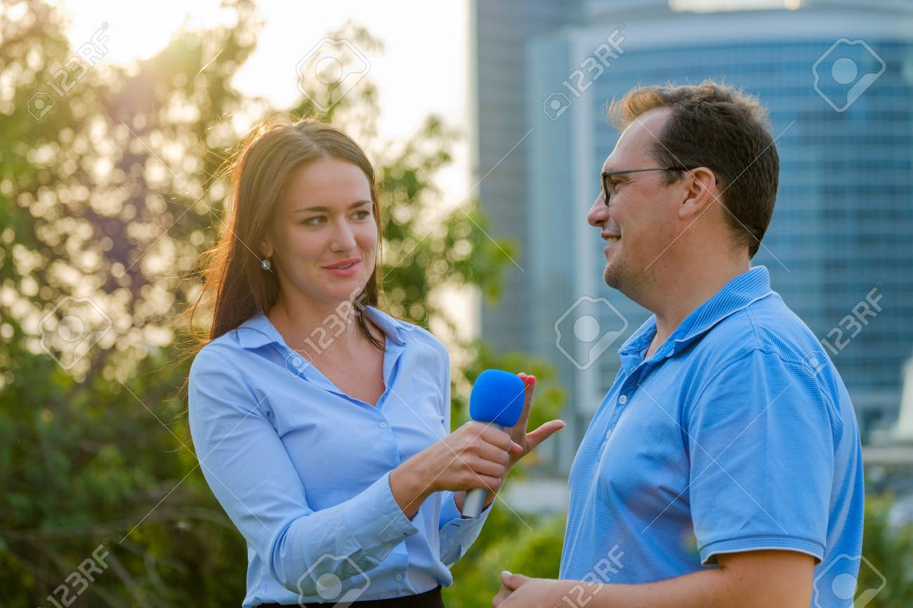 Young girl TV reporter interviews a man - 87279448