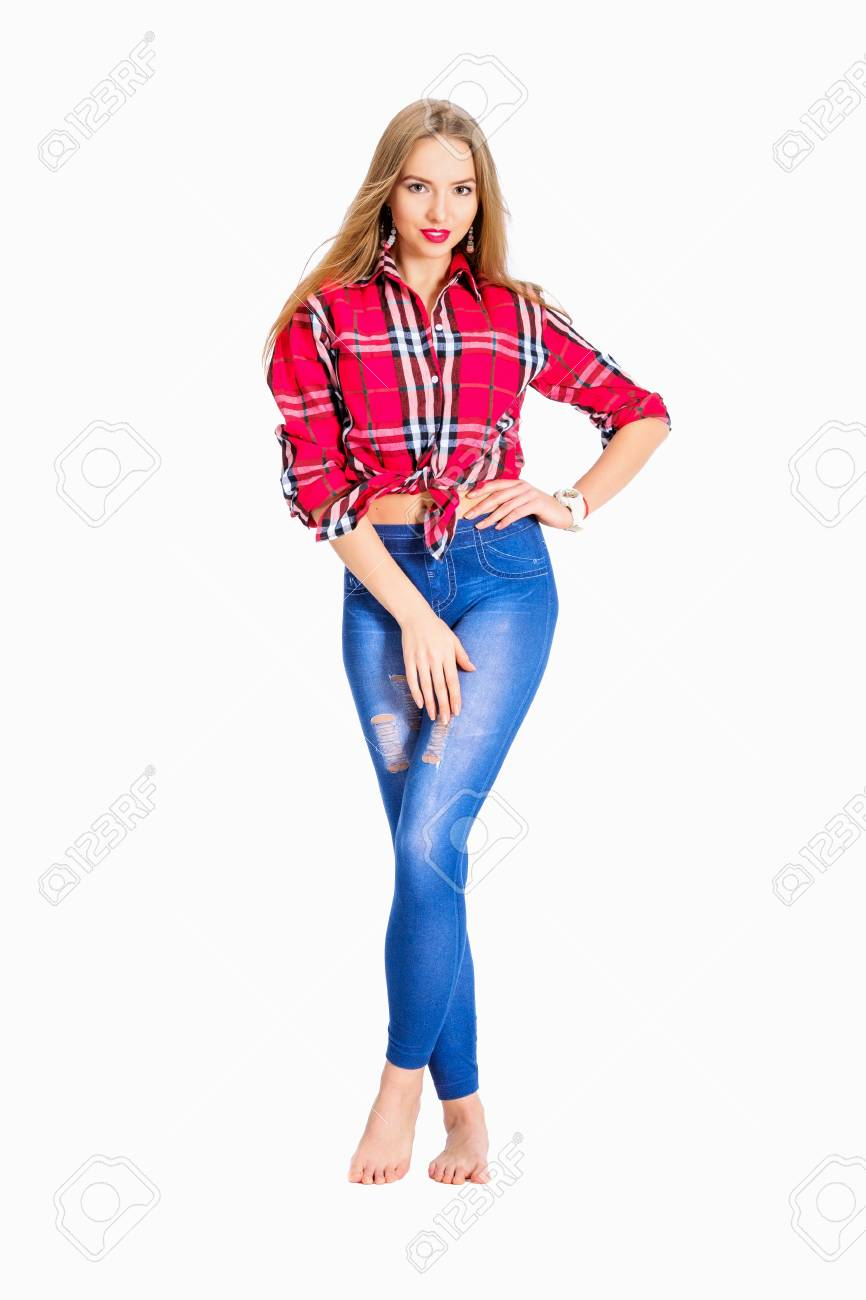 3477b02d484 Young sexy woman dressed in jeans and checkered shirt posing in studio  isolated on white Stock