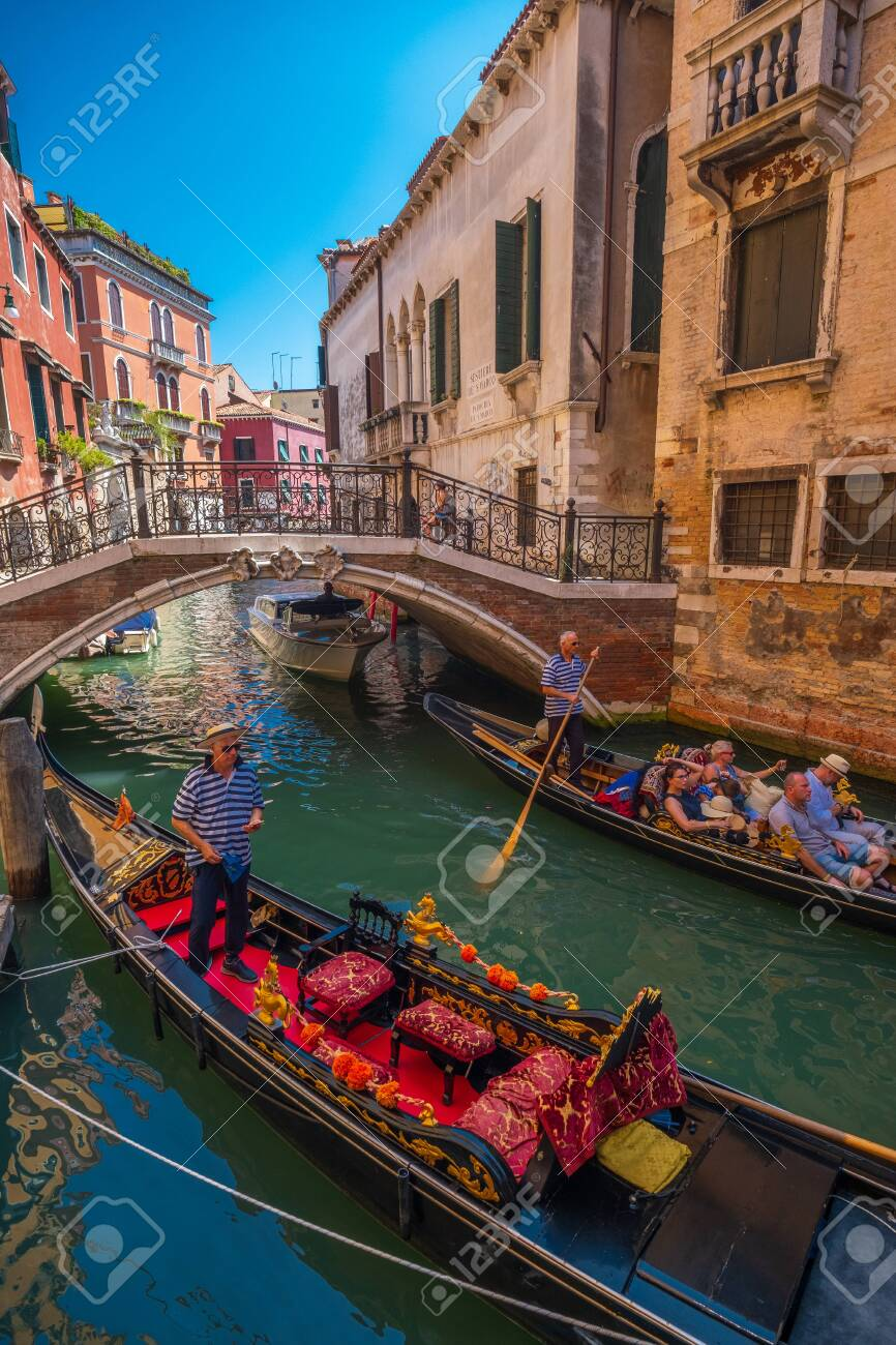 Venice, Italy - August 3, 2019: Gandolier riding tourists on gondola at sunny summer day - 138949030