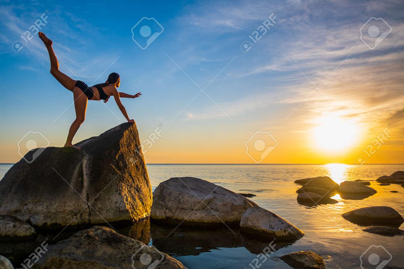 Full length slim female balancing on rock in Virabhadrasana pose against sunset sky during yoga lesson near sea - 163148240