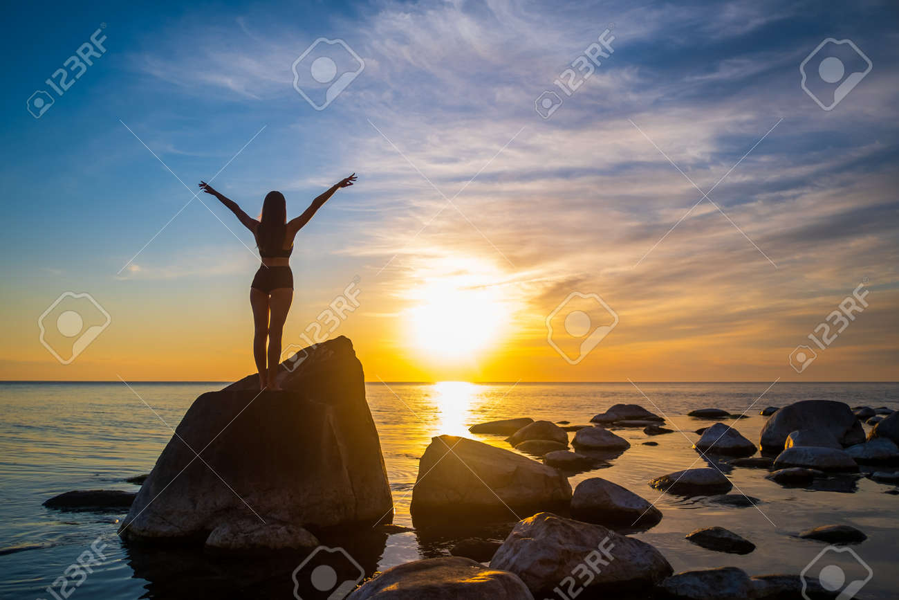 Back view of anonymous female with outstretched arms standing on boulder near calm sea and enjoying freedom against cloudy sundown sky - 163148242