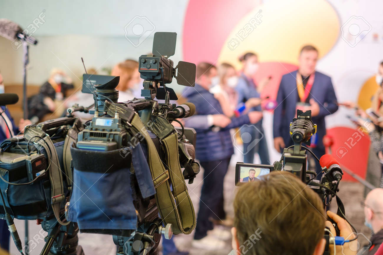 Professional cameras shoot male entrepreneur speaking with reporters during business seminar in modern hall - 166232716