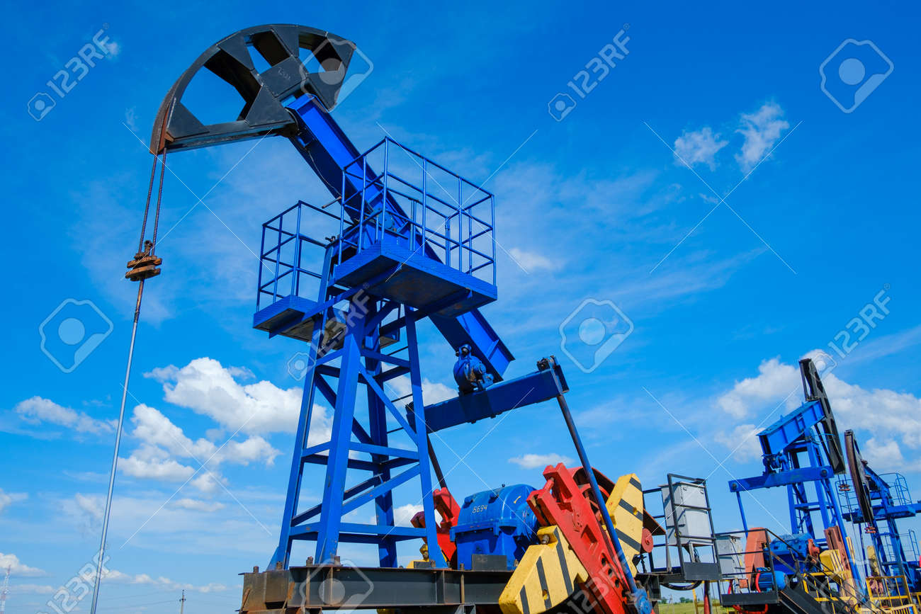 From below industrial machinery pumping oil from wells against cloudy sky on sunny day in countryside - 166158214