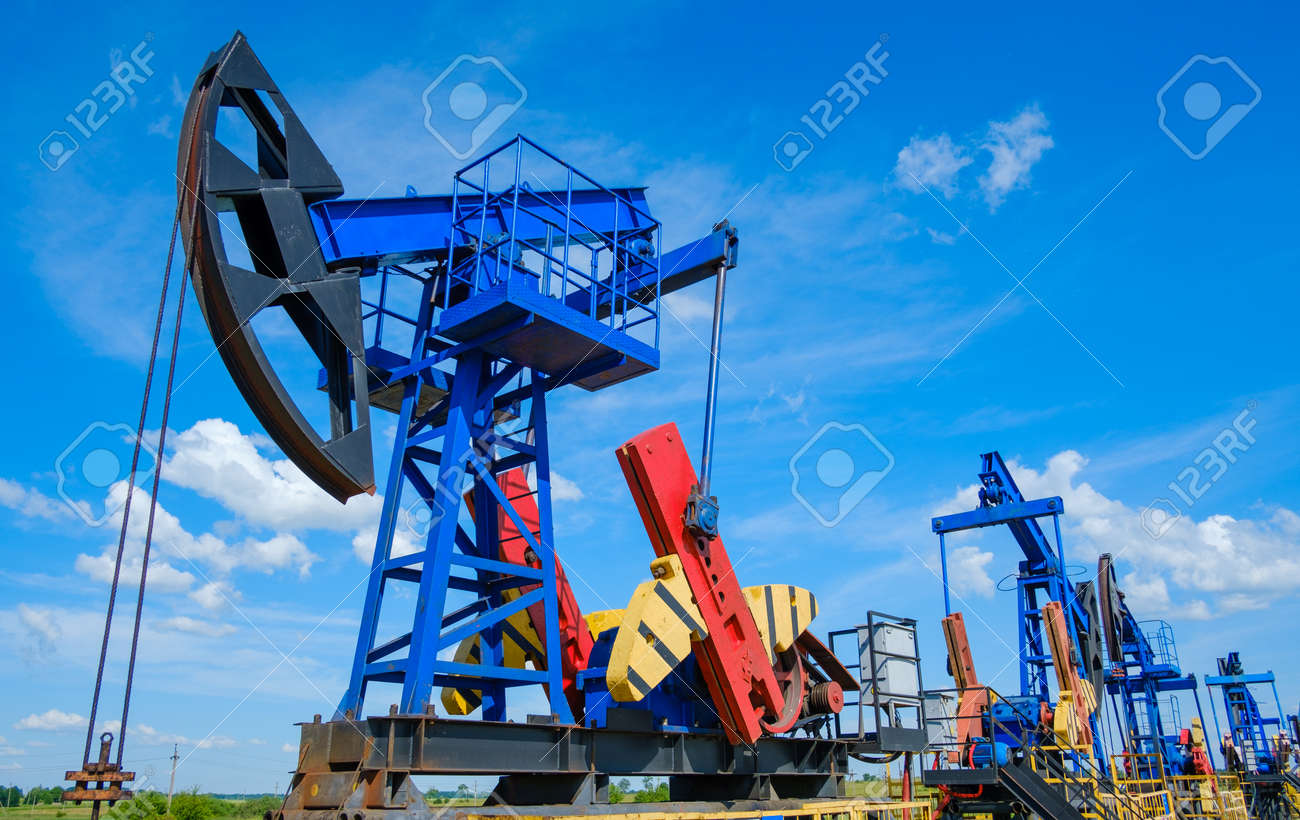 From below industrial machinery pumping oil from wells against cloudy sky on sunny day in countryside - 166232728
