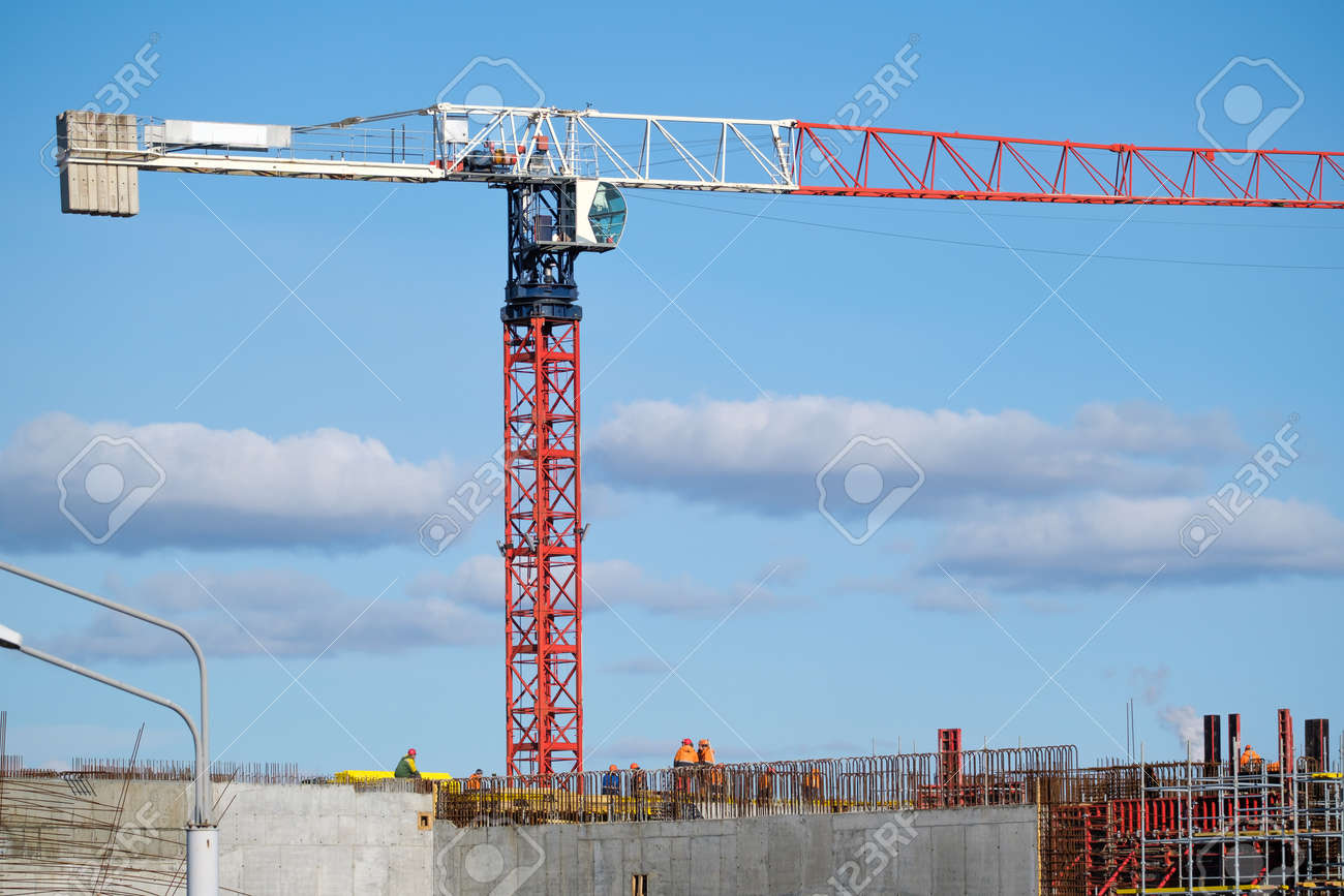 Tall crane located near unfinished building walls with builders against cloudy blue sky on construction site - 166802182