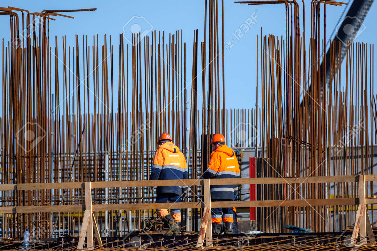 Back view of anonymous men in uniform walking near wooden railing and metal poles during work on construction site - 166802183