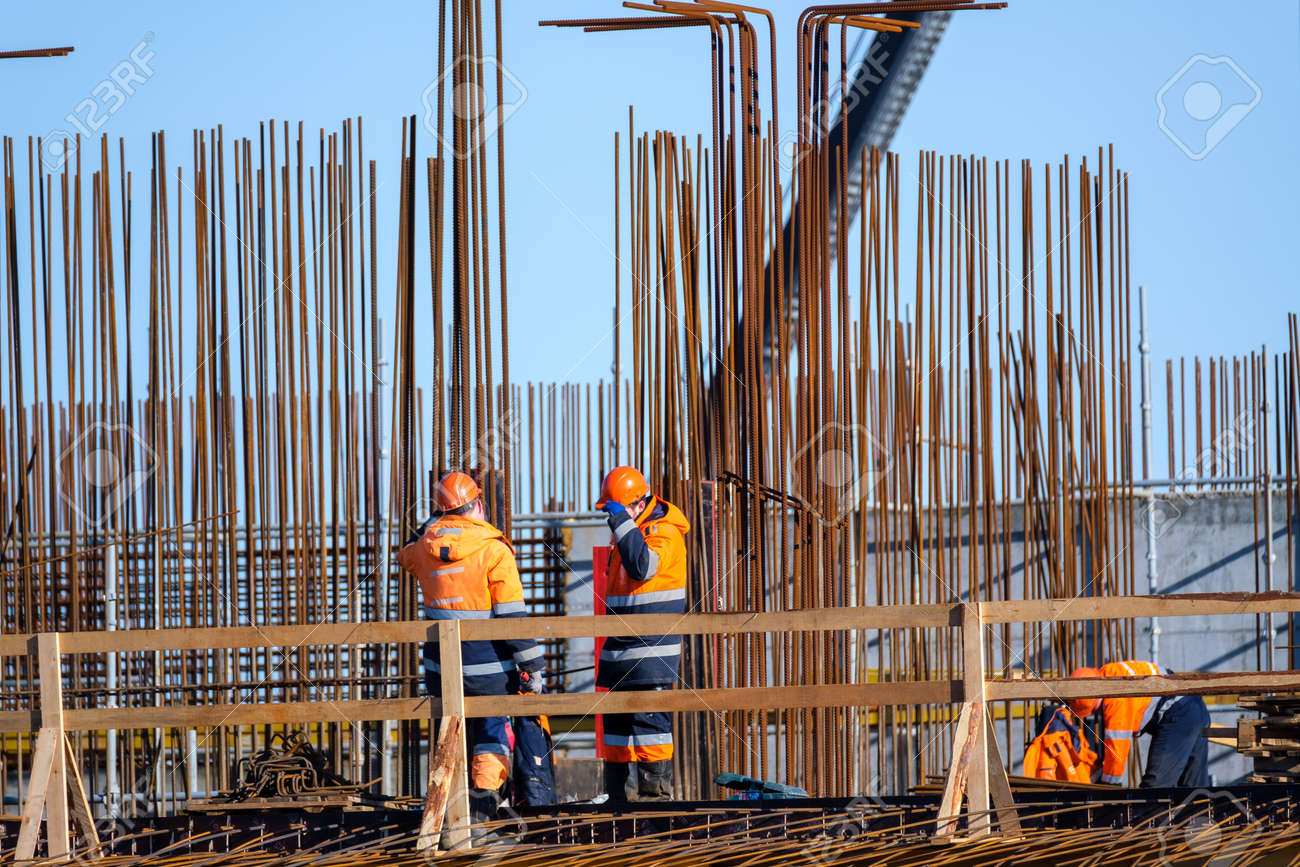 Anonymous male builders in uniform working on bridge near metal poles against cloudless blue sky on construction site - 166802191