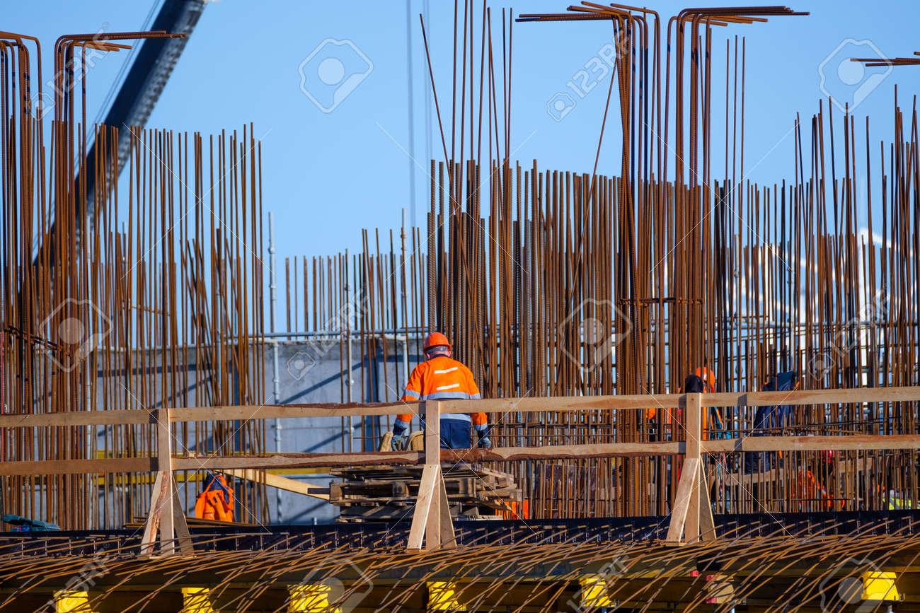 Anonymous men in uniform working on bridge near metal poles outside unfinished building on sunny day on construction site - 166802195