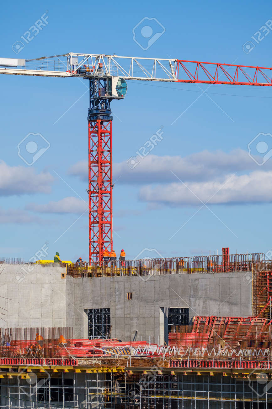 Tall crane located near unfinished building walls with builders against cloudy blue sky on construction site - 166806247