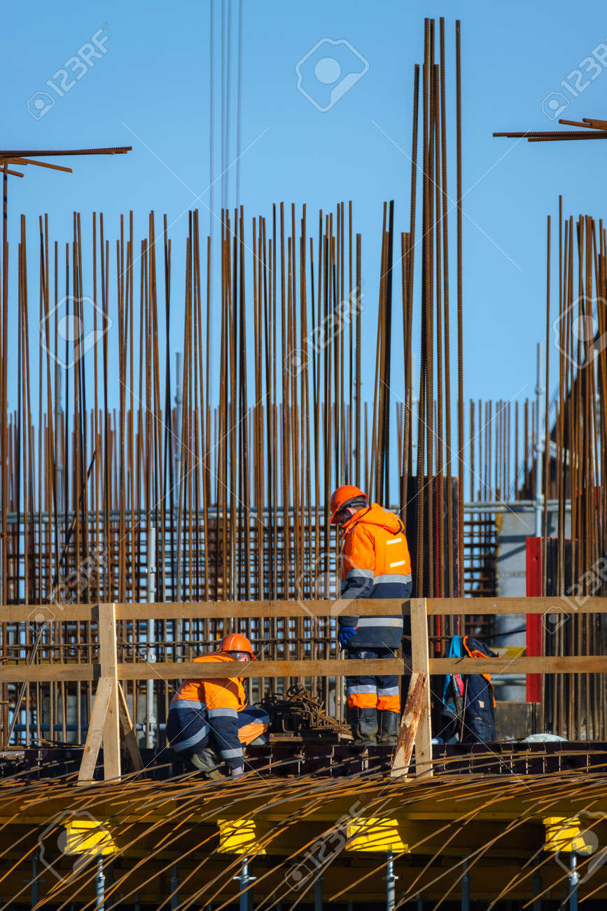 Anonymous men in uniform working on bridge near metal poles outside unfinished building on sunny day on construction site - 166806090