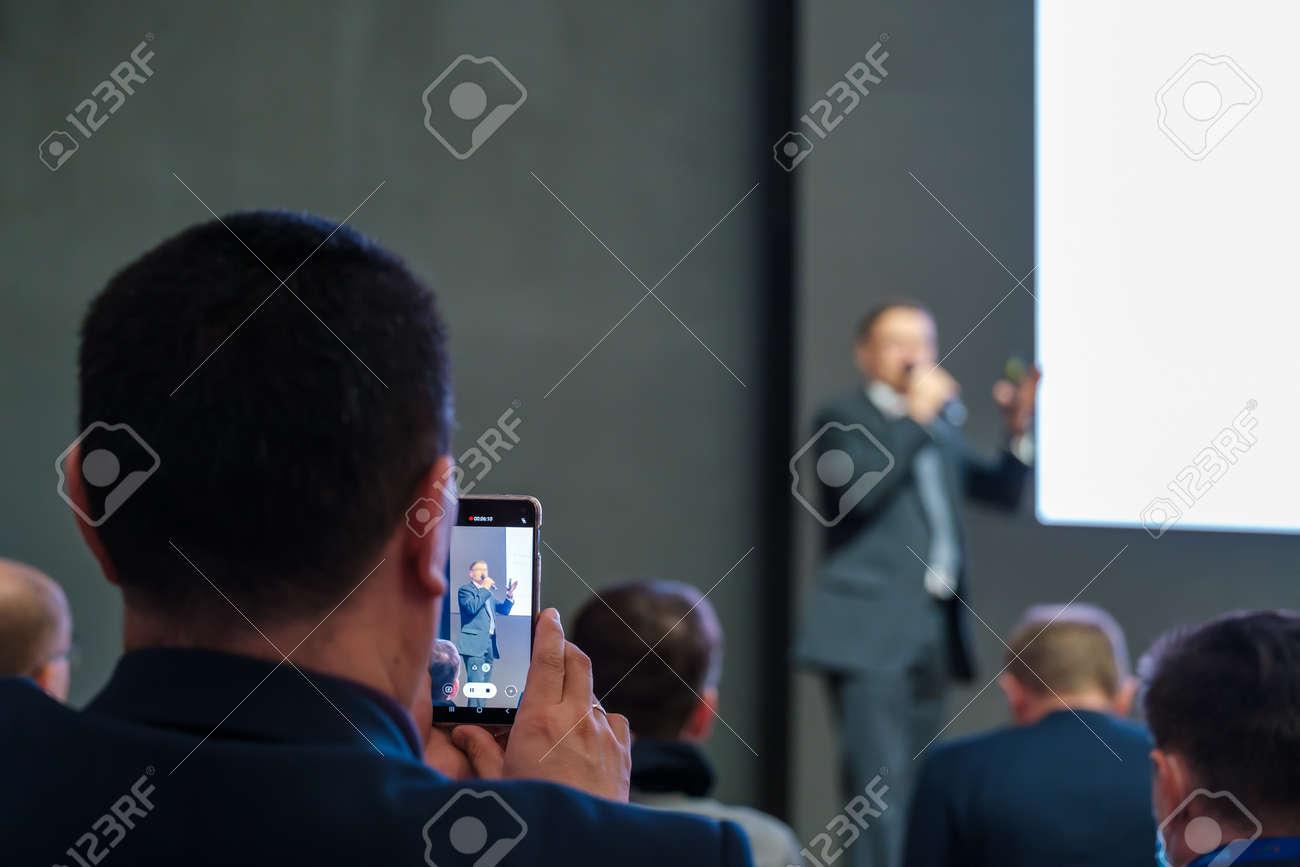 Unrecognizable man shooting speaker during business seminar - 170146783