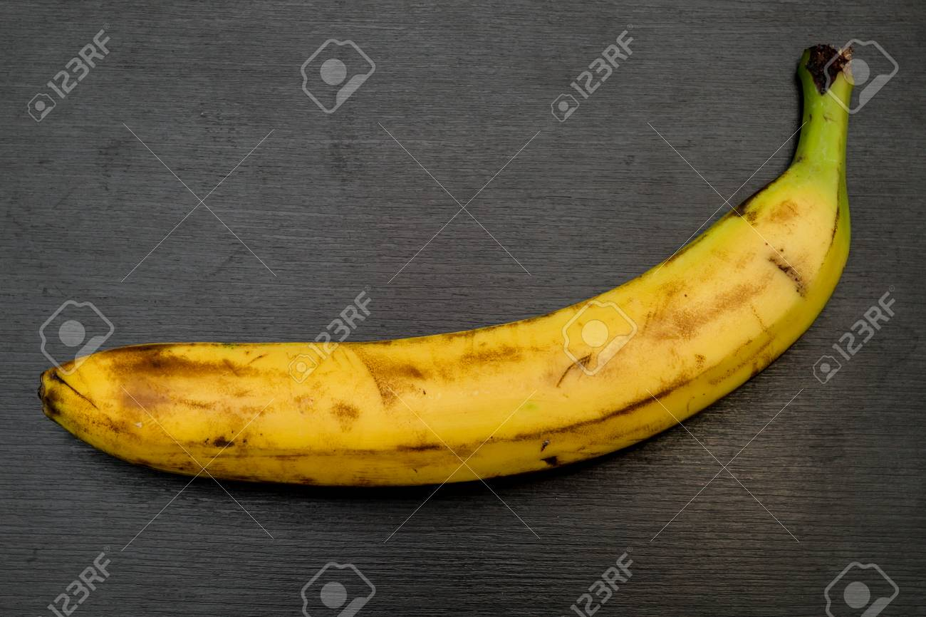 Banana On Table A fresh single banana on grey kitchen table Stock Photo - 84446237