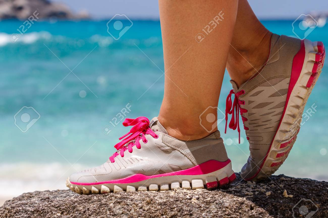 Runner woman stands on a rock near the blue sea. Red laces gray sneakers. Closeup. Photo knee - 91542577