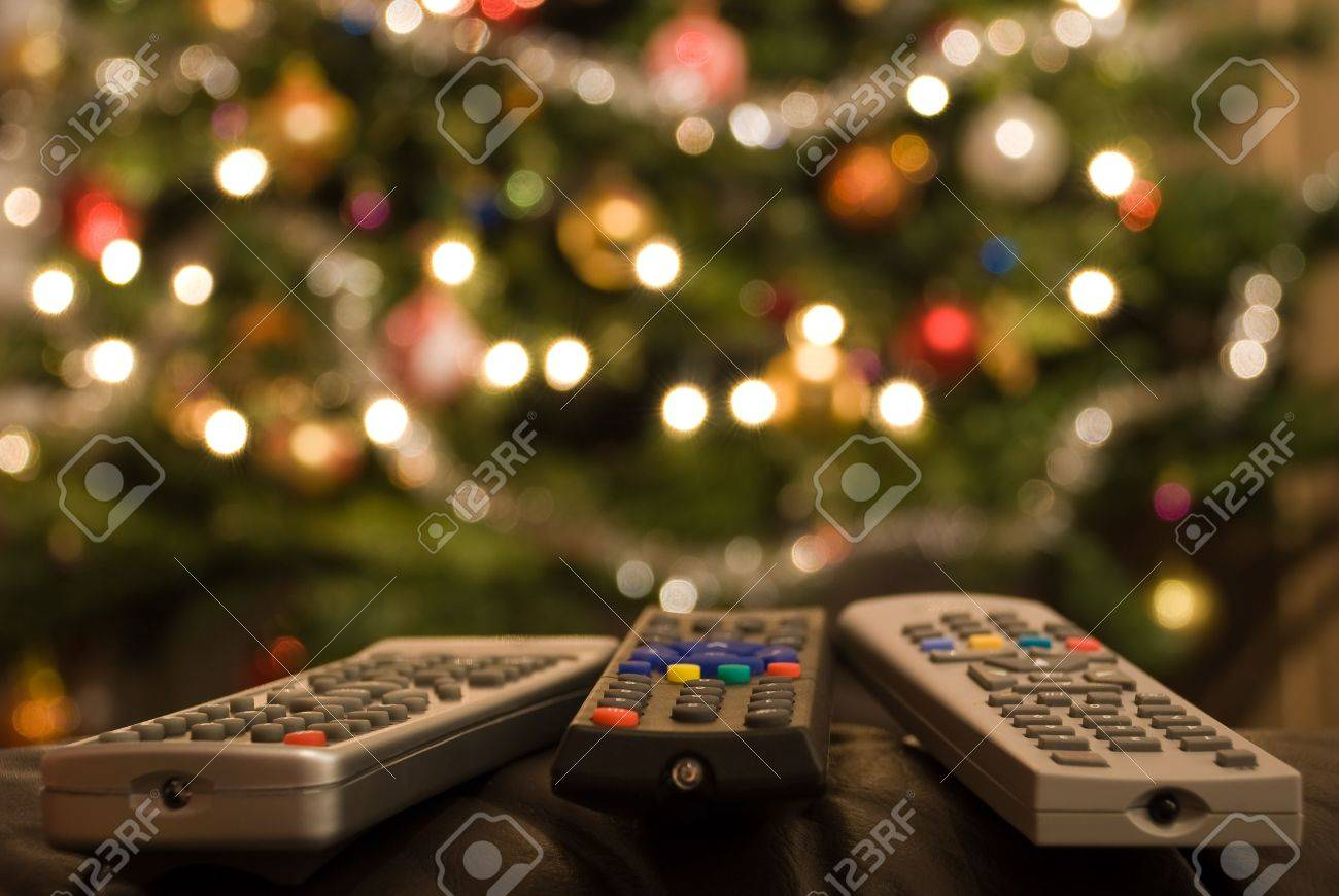 stock photo three remote controls in foreground of christmas tree with lights colorful decorations and balls full of wellbeing peace coziness and