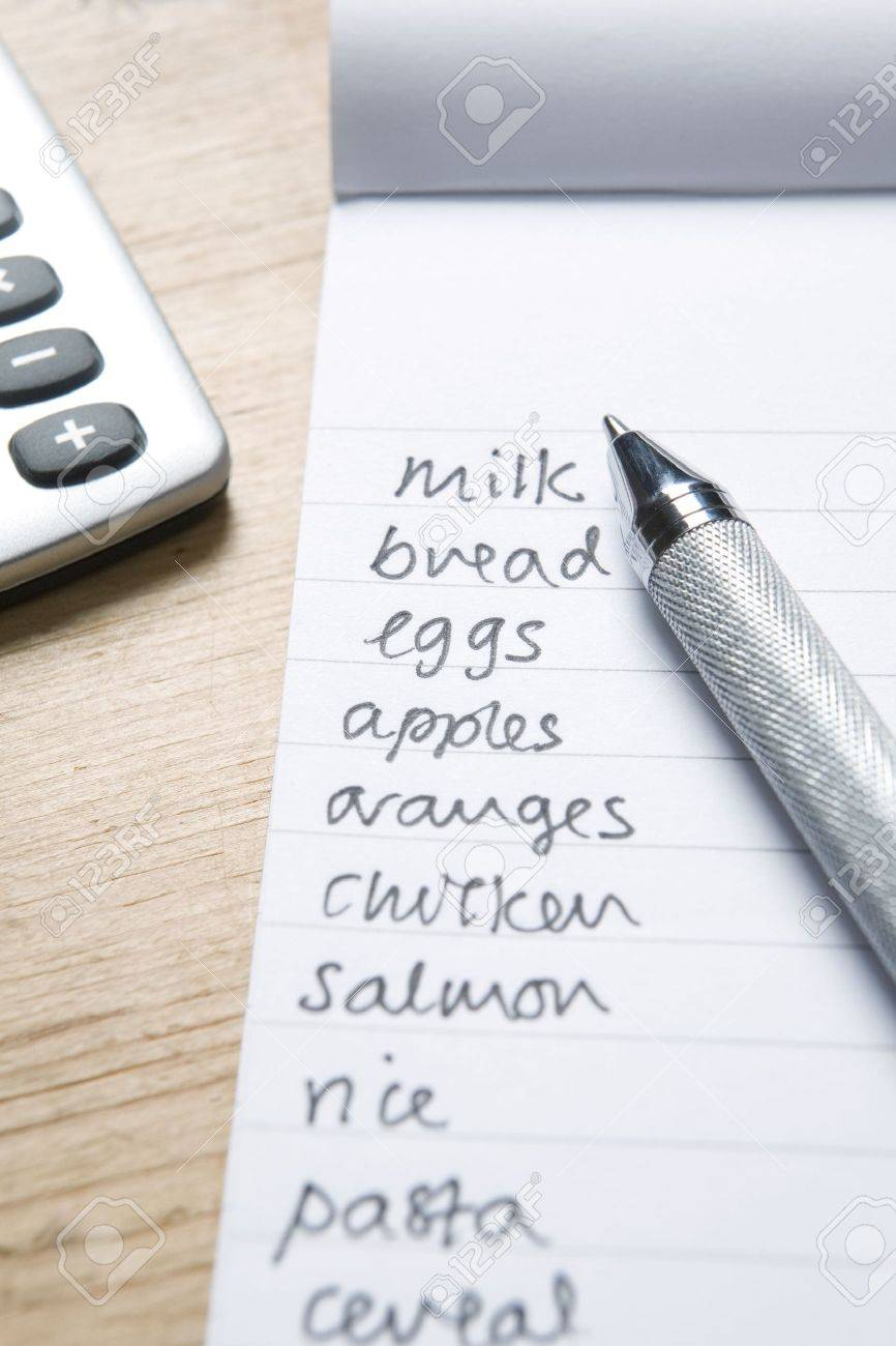 handwritten shopping list with pen and calculatot stock photo