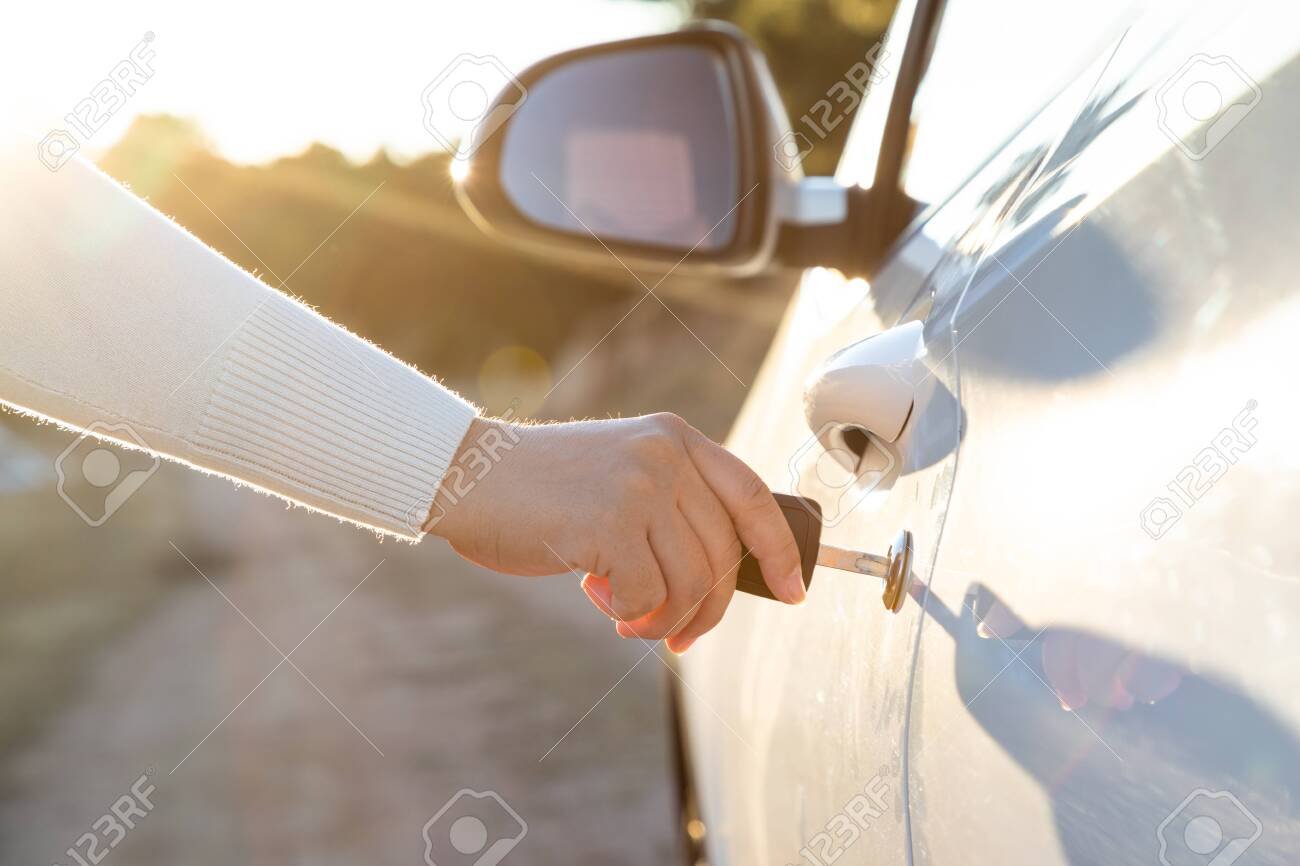 Woman takes the key to drive the door of the car - 129894603