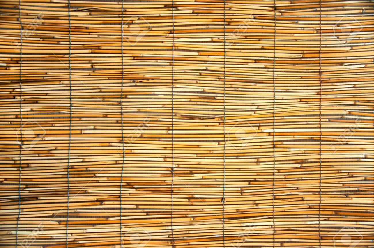 Tessitura di un tappeti arancioni fatti di bambù e corda