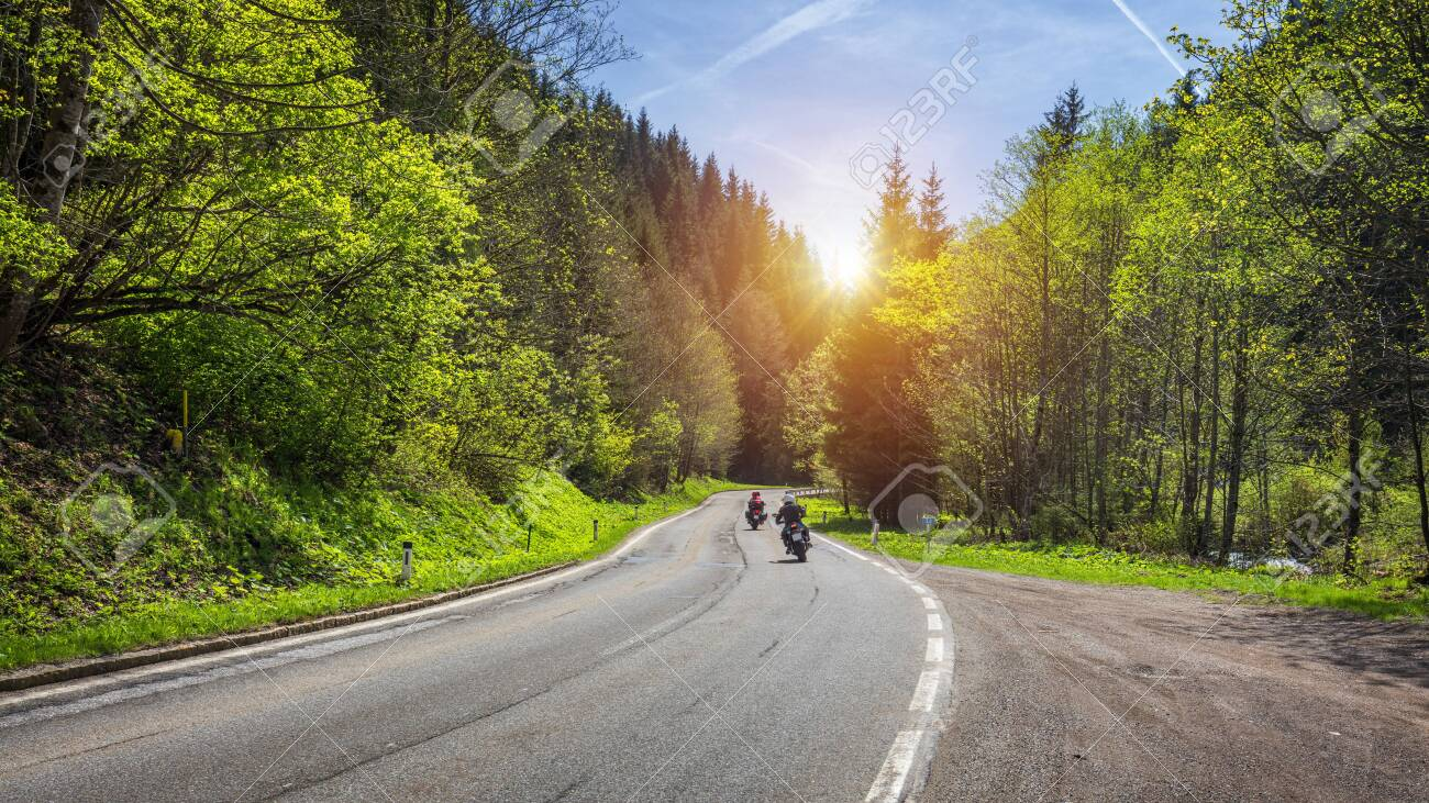 Bikers on mountainous highway, biker on the road in sunset light riding on curve road pass across Alpine mountains, extreme lifestyle, freedom concept. Austria, Alps - 123274771