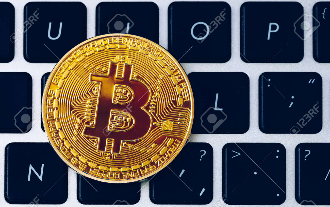 Bitcoin on compuer keyboard in background, symbol of electronic virtual money and mining cryptocurrency concept. Coin crypto currency bitcoin lies on the keyboard. Bitcoin on keyboard. - 168255337
