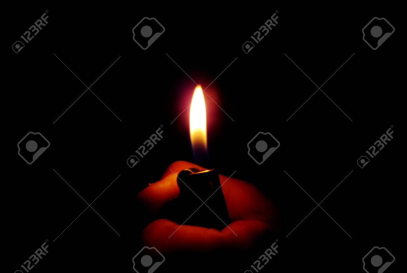 Flame Of A Lighter In The Dark Light And Shadow Stock Photo