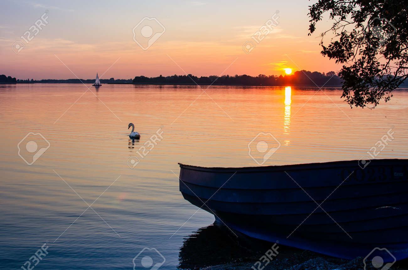 Masurian lake, sunset, motor boat on the lake shore. In the distance a swan and a sailboat - 168433459