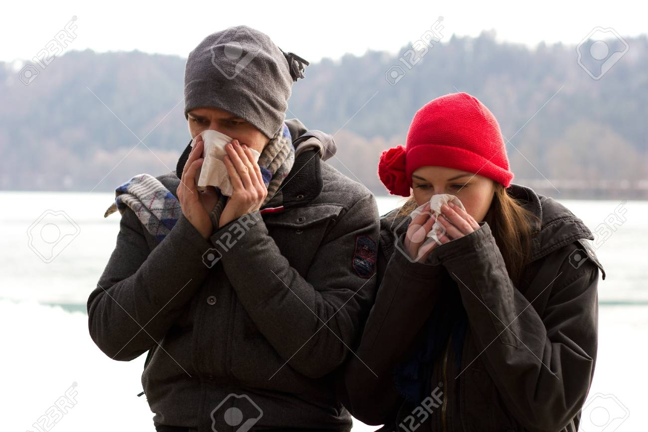 A Young Couple Next To Each Other Blowing Their Noses Stock Photo - 11884862