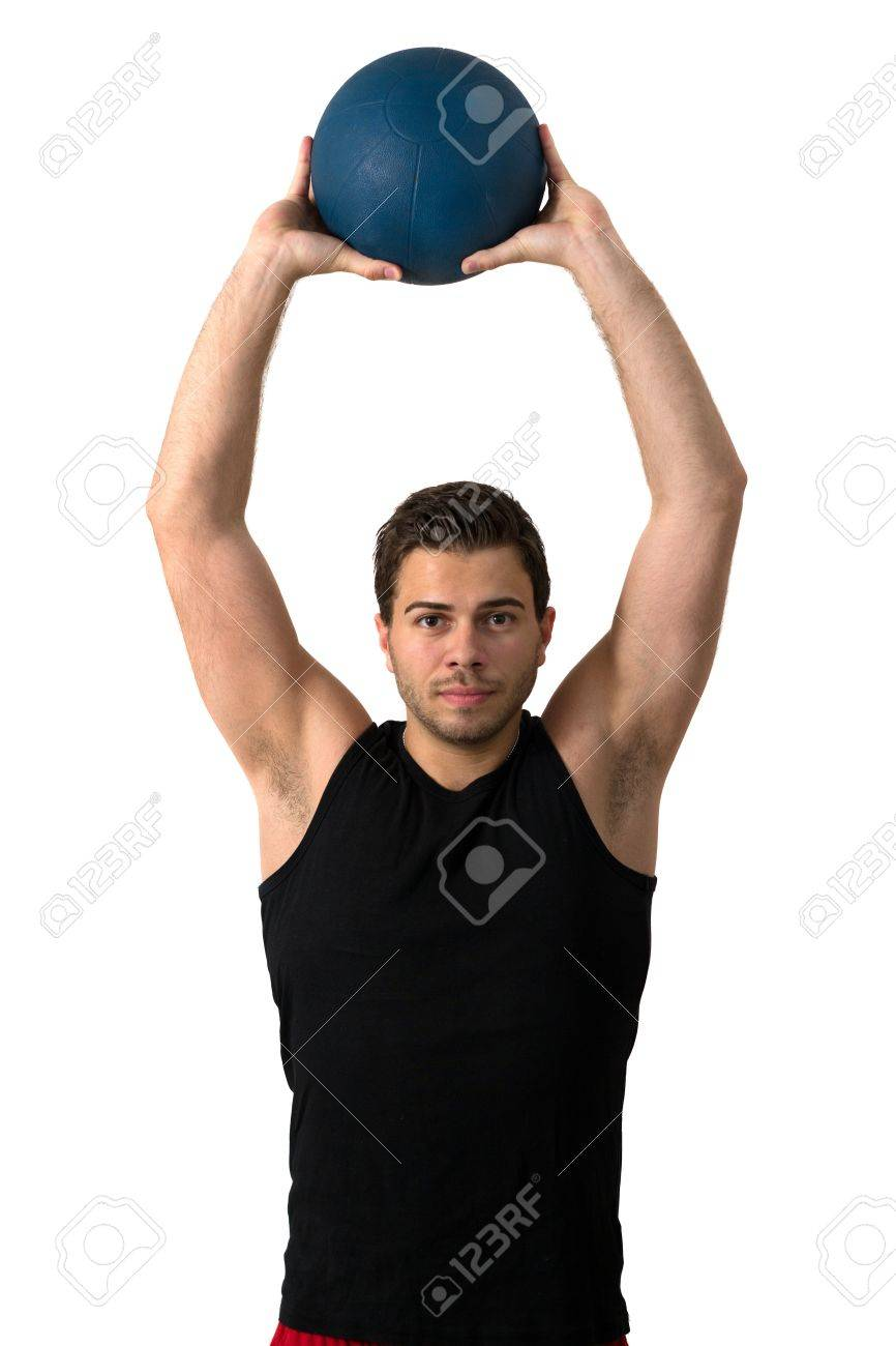 Attractive brunette man in a black tank top and red pants working out with a medicine ball Stock Photo - 14158743