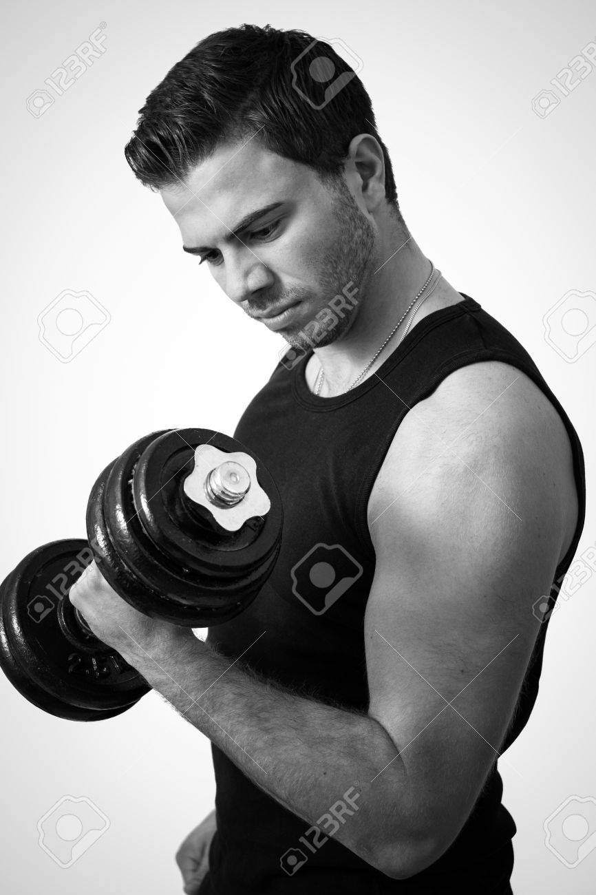 Young attractive man pumping weights in a black tank top Stock Photo - 14749641