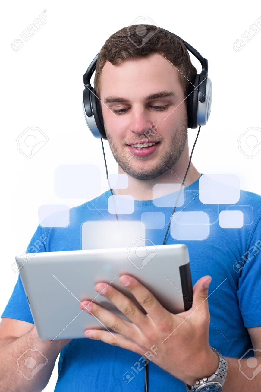 Young man with headphones and blue t-shirt working on a tablet pc Stock Photo - 14802715