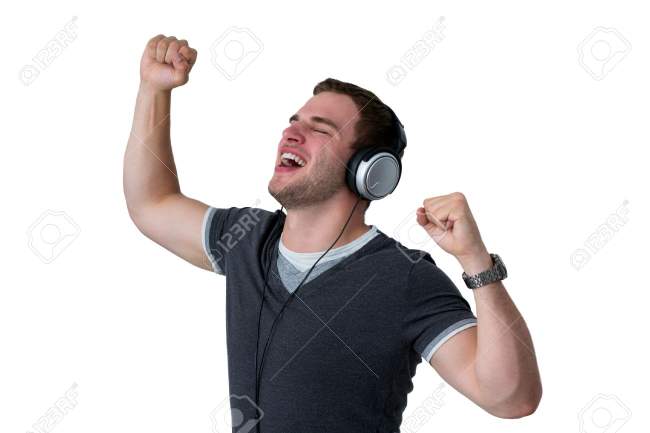 young man listening to music and dancing with arms in air stock