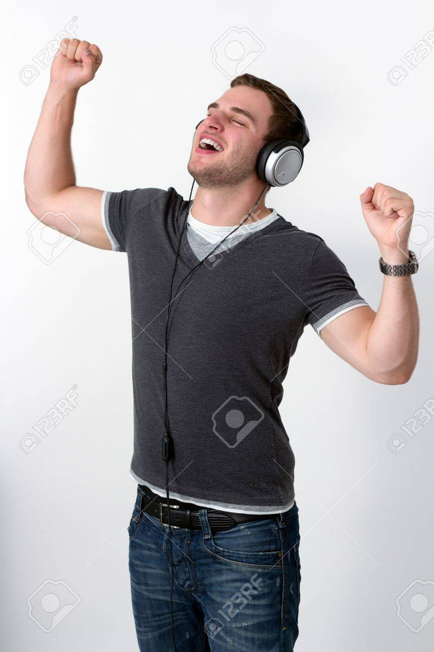 Young Man Listening to music and dancing with arms in air Stock Photo - 16375056
