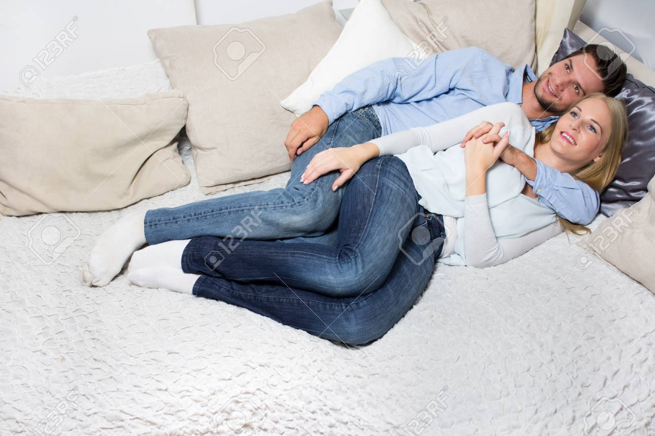 Young Couple lying On A Couch and looking at the camera Stock Photo - 16883808