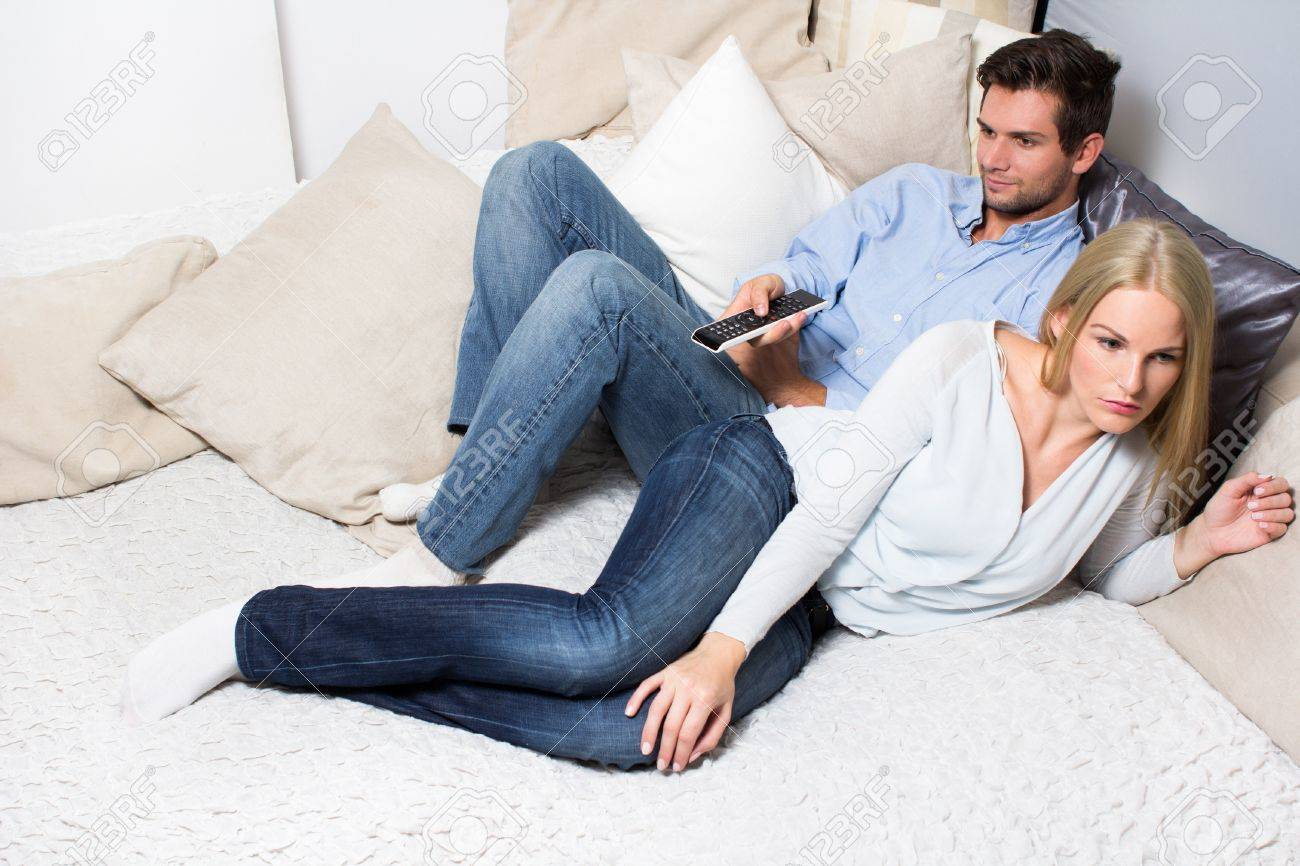 Young Couple lying On A Couch. Man watching tv and woman is annoyed Stock Photo - 16883857
