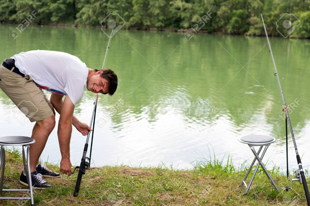 Brunette Man Fishing at a lake with green water Stock Photo - 16883873