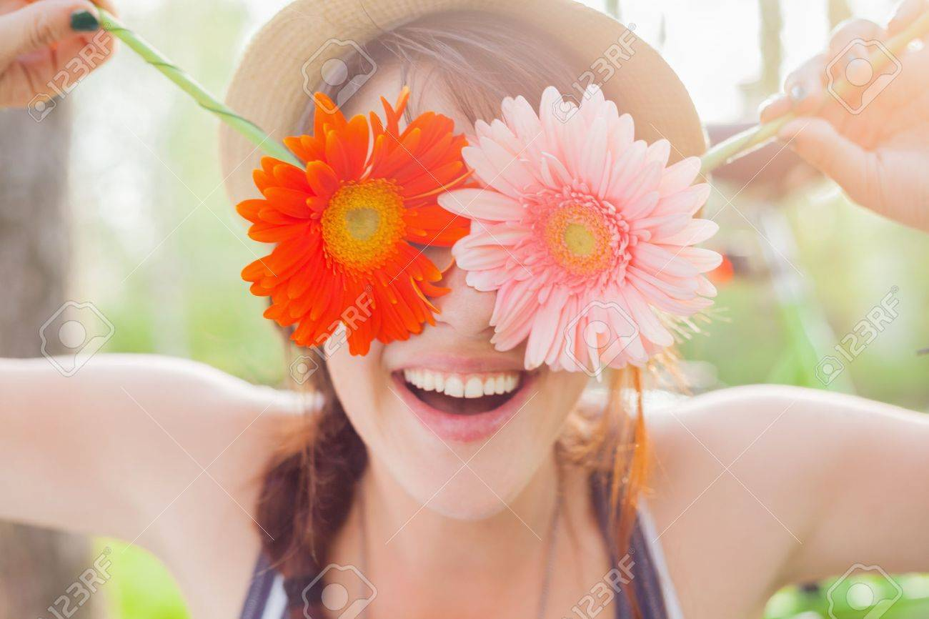 Young woman covering her eyes with fresh colorful flowers. Enjoying..