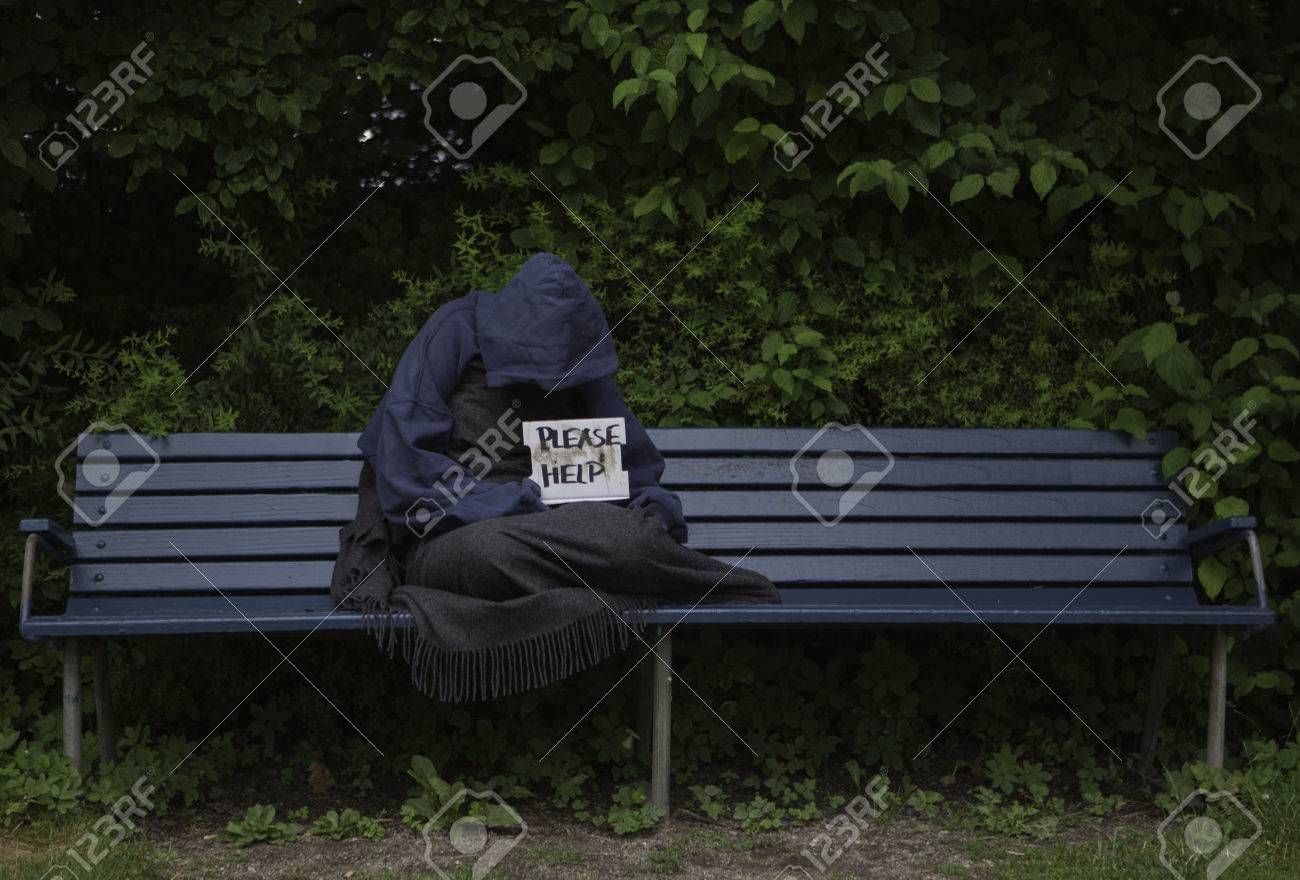 Homeless Man On A Park Bench With A Cardboard Sign Stock Photo