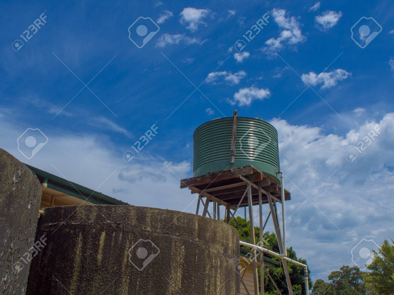 Green Corrugated water tank on a tall stand with blue sky
