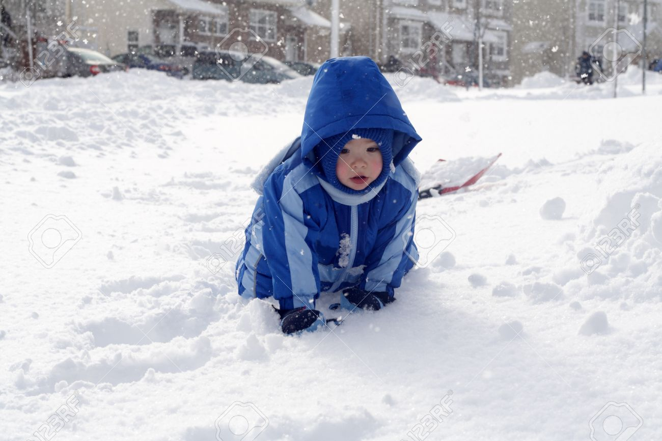 1cecf39a8 A toddler boy wearing a blue snowsuit playing in the snow. Stock Photo -  8683942