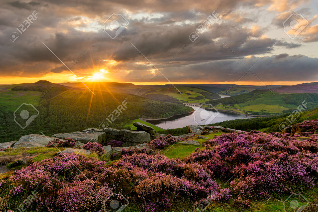 Evening sun bursting through dramatic clouds with epic view of Ladybower Reservoir in the Peak District. - 159217218
