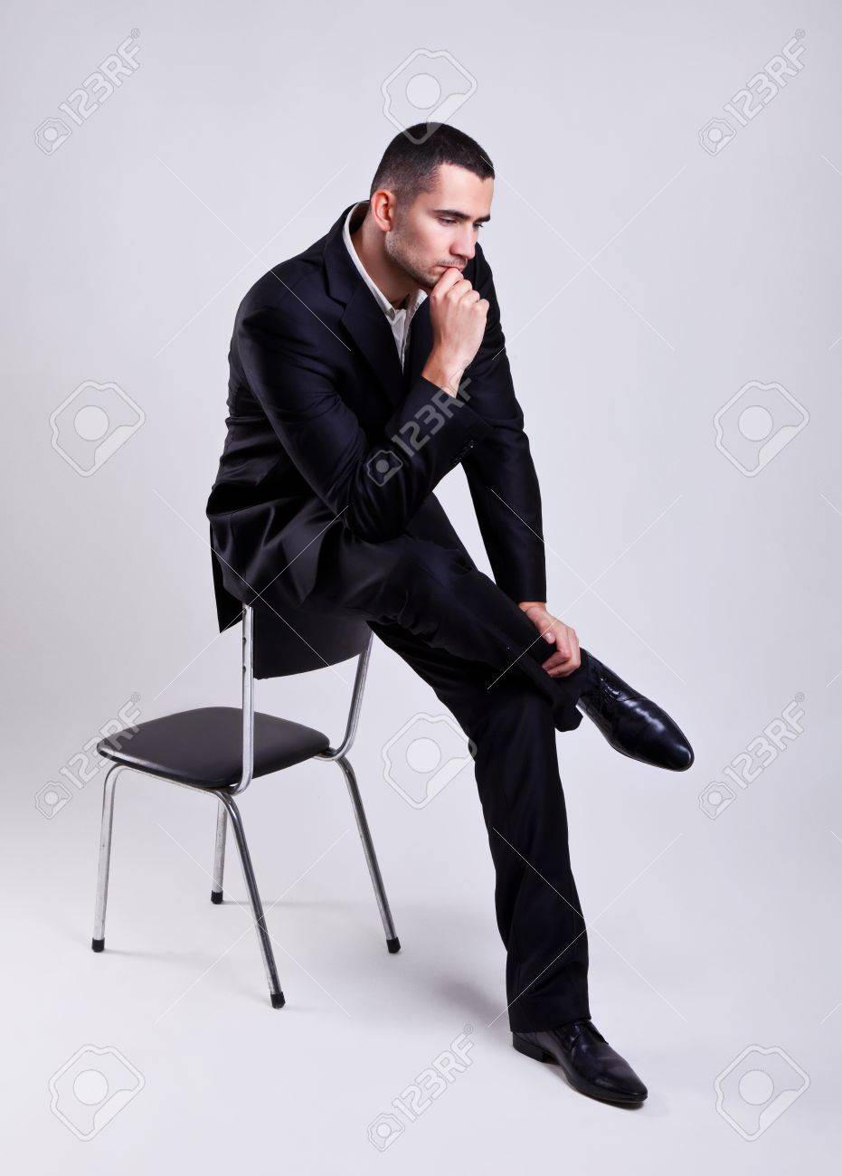 elegant young businessman sitting on a chair and thinking over