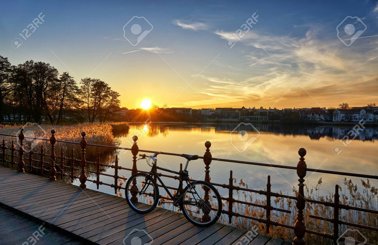 Beautiful sunset at a bridge with a bicycle. - 130754762