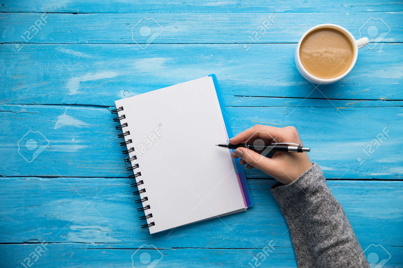 woman hand notepad and coffee on desk - 155725775