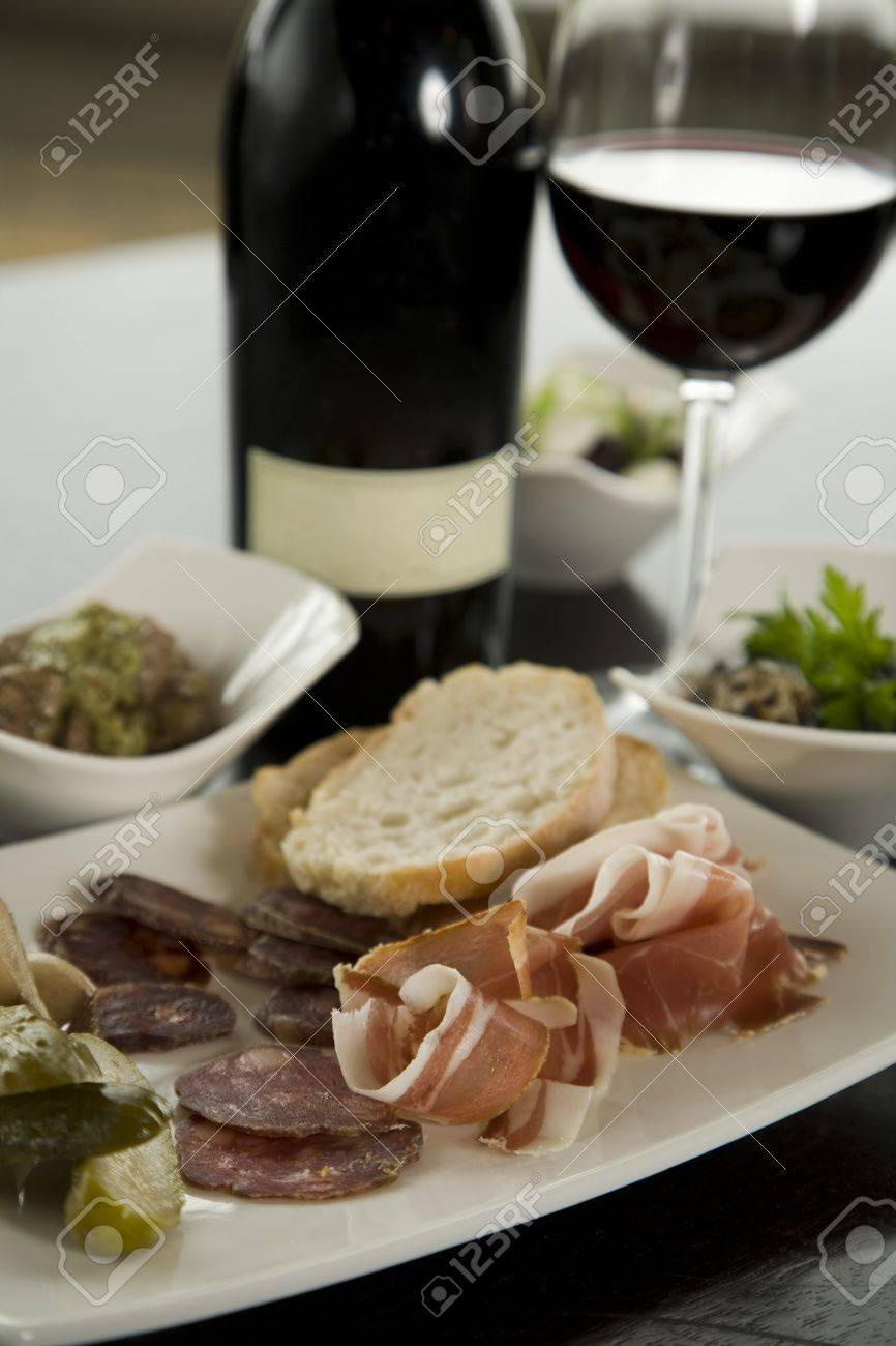 Tapas and red wine pairing in small white bowls on dark table. Stock Photo - 10876686